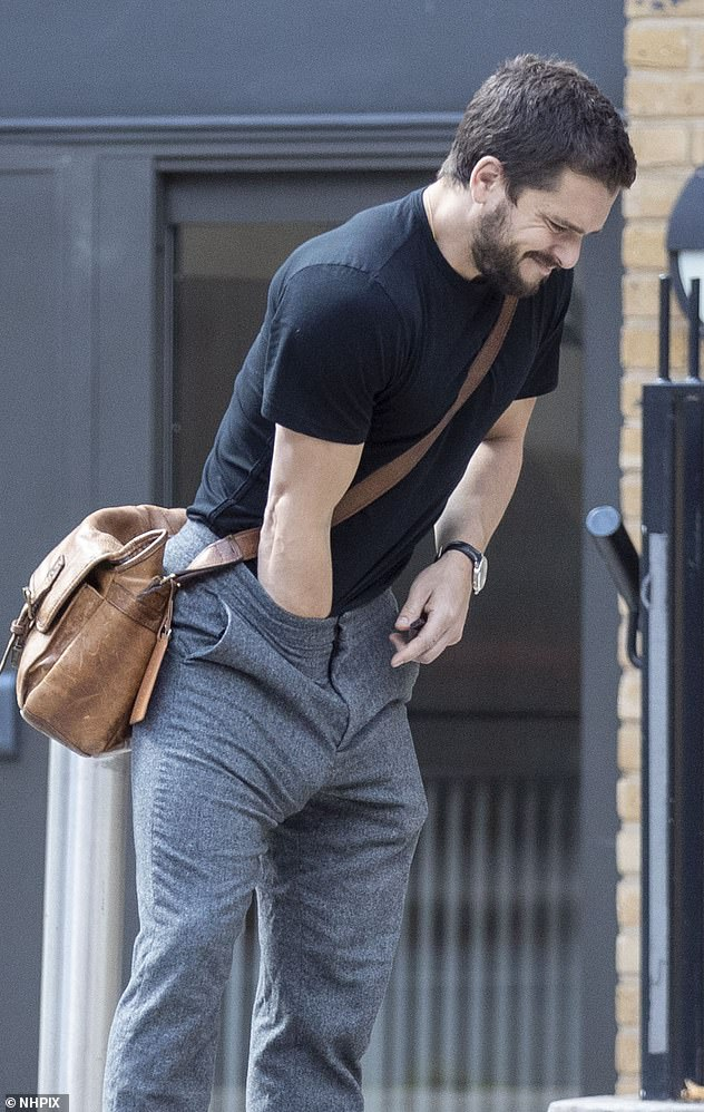 Awkward: Kit wore a fitted black T-shirt tucked into slate grey slacks